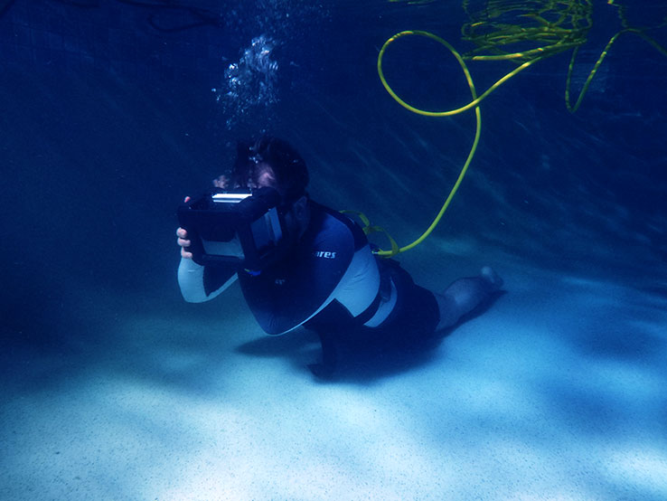 A diver is pictured, underwater in a swimming pool while wearing Raytracer's Titan Lake virtual reality headset.