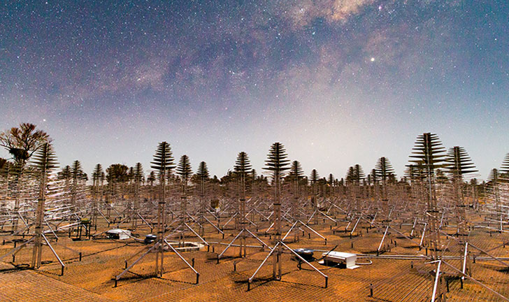 Wide angle image of metal Christmas tree-like antennas on red soil with the stars of the Milky Way overhead.