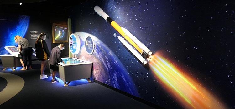A poster of a rocket on a wall behind a child looking at a display cabinet.