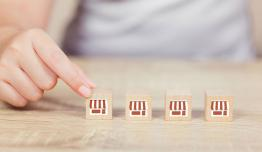 Four wooden blocks decorated to look like shops